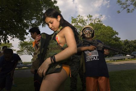 Nina Berman - Girl and boy at US Marines weapons display